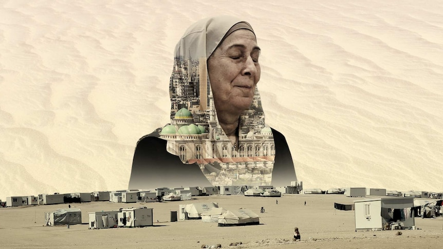 You view a woman in a hijab with closed eyes looking over a sparse refugee camp in the desert.