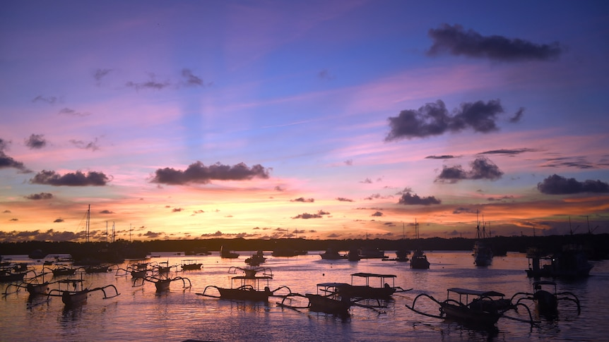 Boats drift in a small port at sunset in Bali.