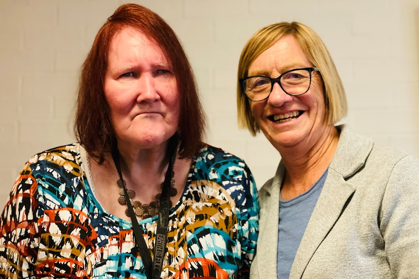 Two women smile for a photo together. One on the left has red hair and the one on the right has blonde hair