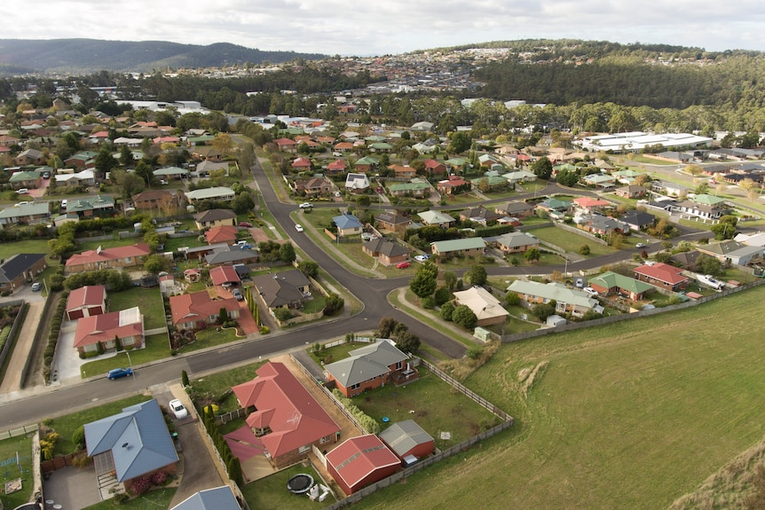 A birds eye view of houses and schools next door to a paddock.