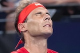 Spain tennis star Rafael Nadal closes his eyes and winces during a match at the ATP Cup.