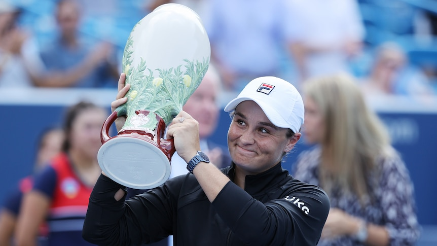 Ash Barty holds a large white trophy and smiles