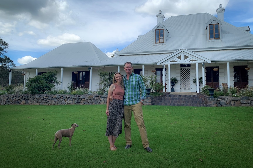 Man, woman and dog standing in front of country homestead.