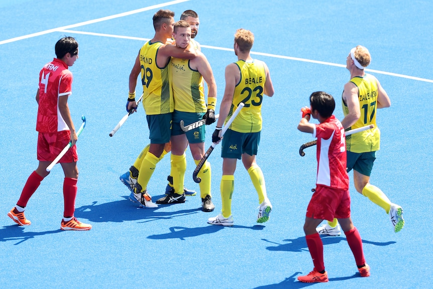 Hockey players hugging in celebration after getting a goal during a match