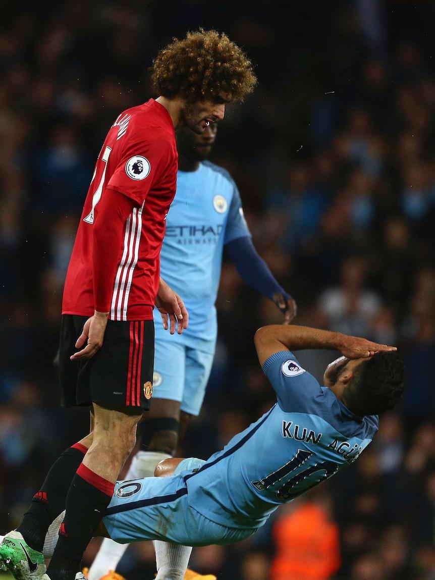 Sergio Aguero goes down after a headbutt from Fellaini