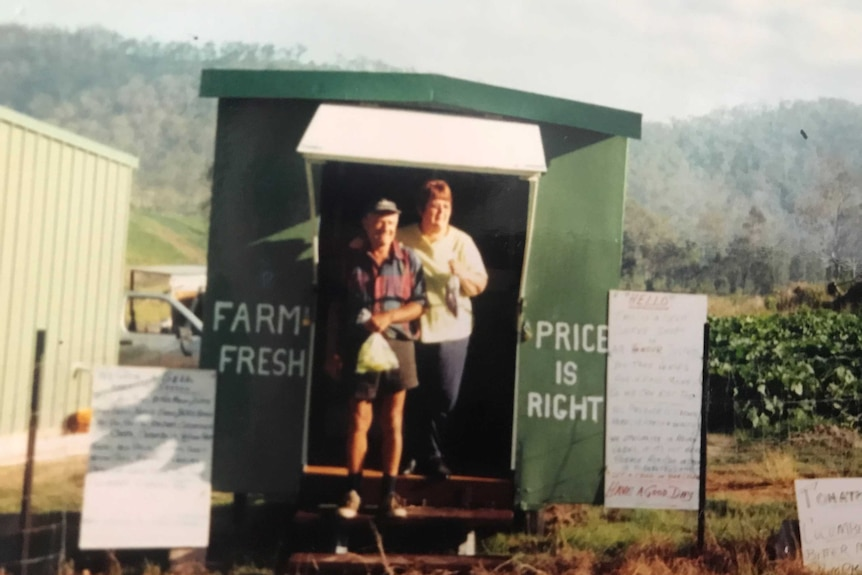 A photo from 1980 of two people out the front of a small shop at a farm