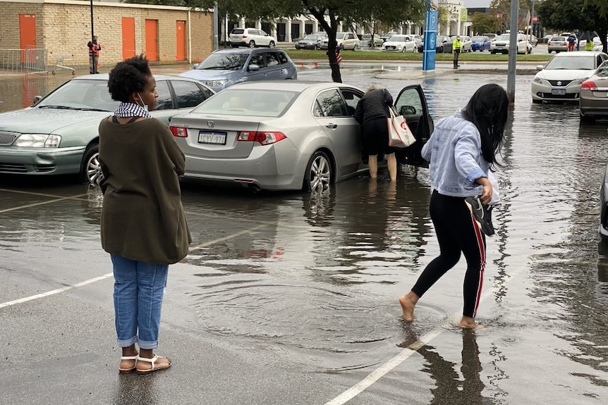 One woman stands watching as another woman wades through a puddle.