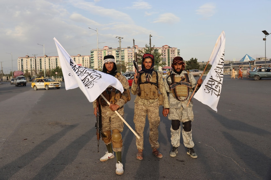Three Taliban fights stand together with white flags.