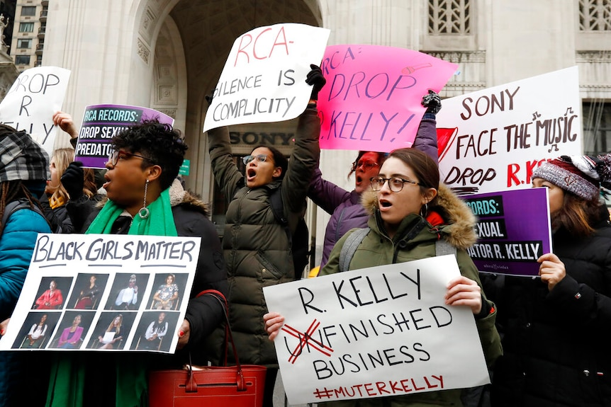 """Women dressed in winter jackets holding handwritten signs with slogans such as """"mute R Kelly"""""""