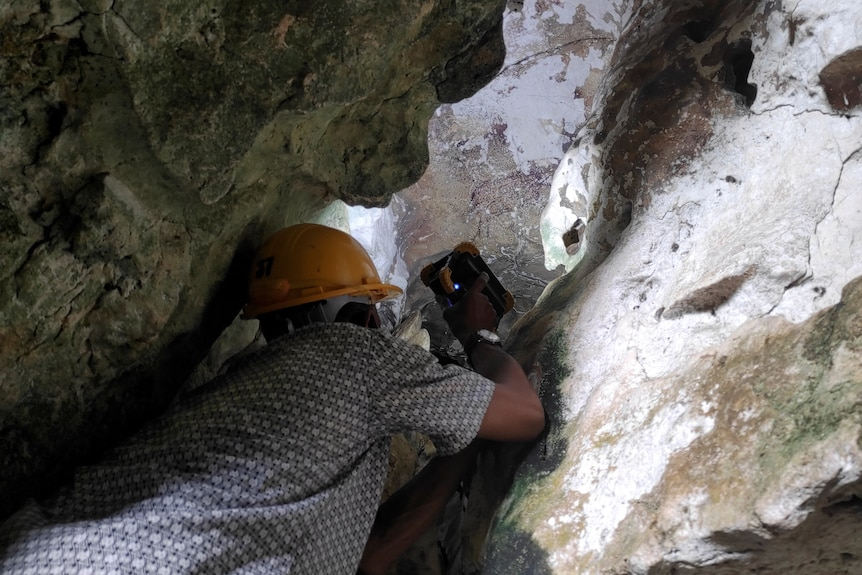 A man in a rocky crevice shines a torch on a cave painting.