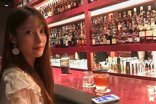 Park Gyu-ri sitting at a bar with a drink in front of her