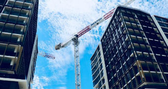 A Meriton crane is shown hanging over tall residential apartments in Sydney.