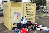 clothes and other donated items on the street next to donation bin