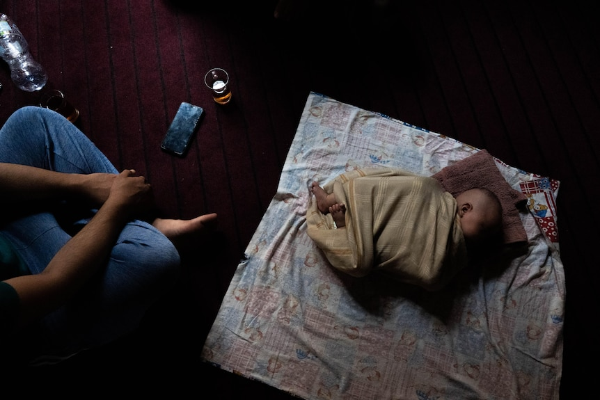 Taken from above, the photo shows a small baby wrapped in cloth sleeping on a plum-coloured carpeted floor.