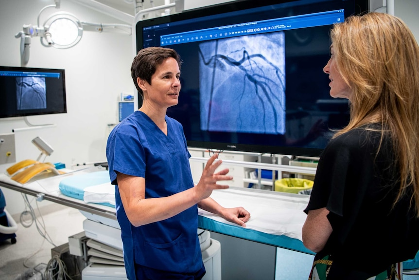 Cardiologist Professor Gemma Figtree shows Jennifer Tucker an image of the blockage in one of her arteries on a large screen.