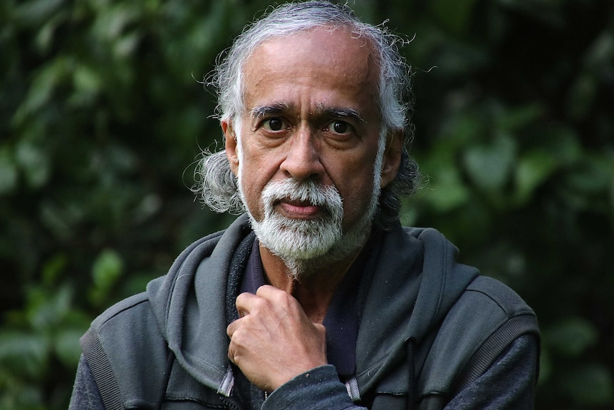 A headshot of Suresh Rajan wearing a grey jumper in front of some trees.