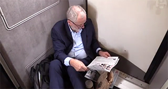 Jeremy Corbyn sits on the floor of a train.