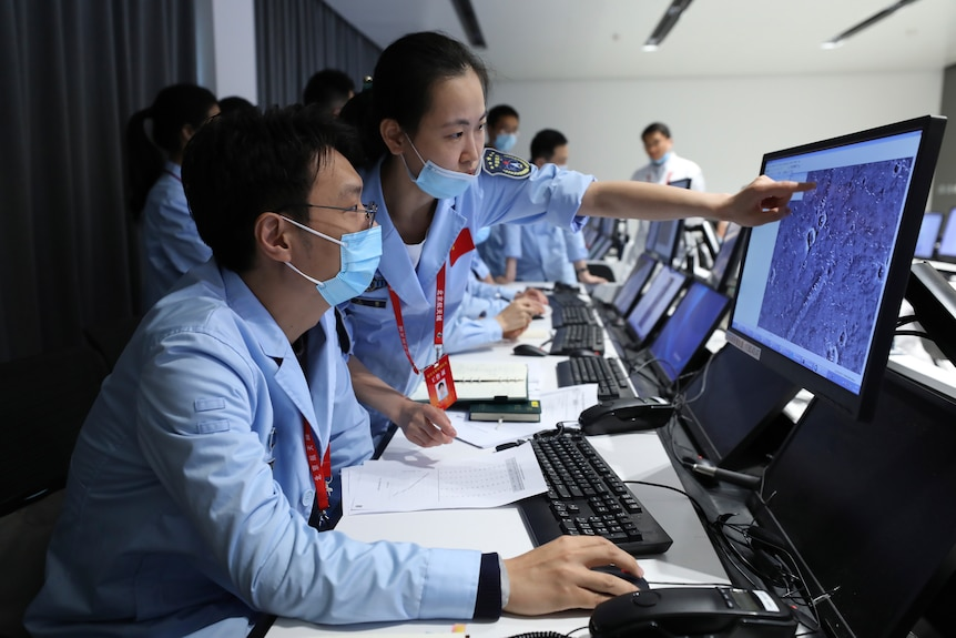 People point at computer monitors and work at the Beijing Aerospace Center.