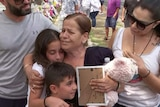 A woman holds two children in an embrace.