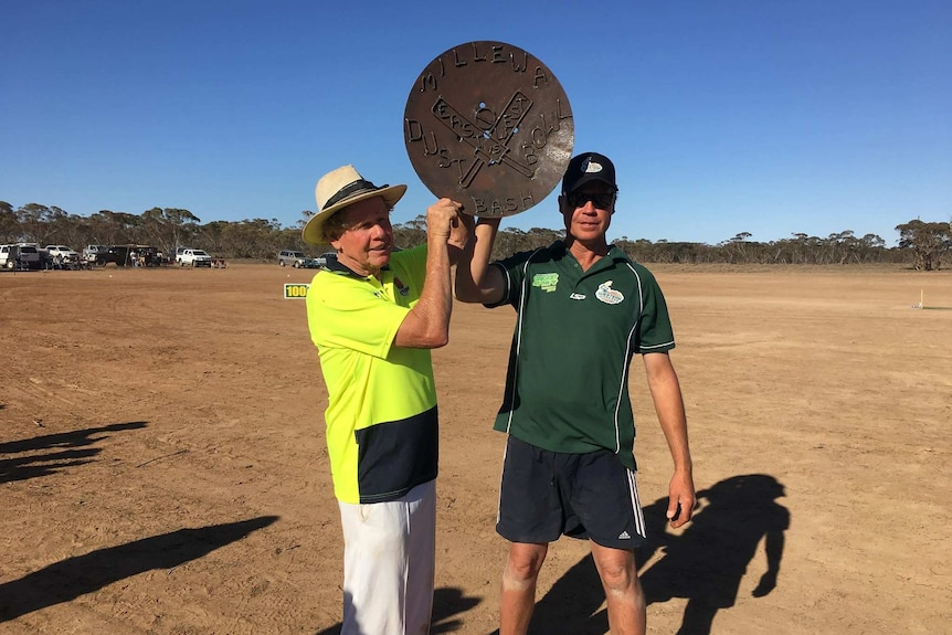 two man holding a piece of metal