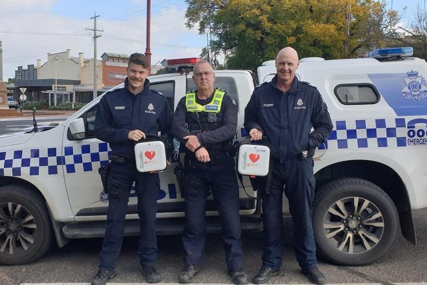 Three ;police officers with a car and defibrillators