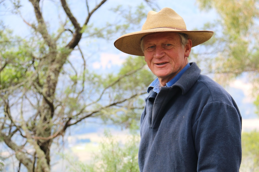 Martin wears a wide-brimmed hat and smiles among the trees.