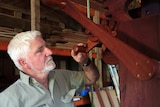 Man with a hand on a wooden turning handle