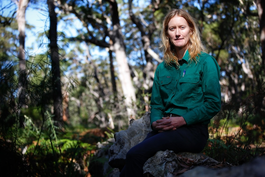 A woman with blonde shoulder length hair wearing a green long sleeved shirt sitting on a rock in a leafy national park