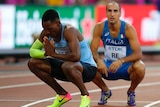 Isaac Makwala crouches on the track with his hands held together.