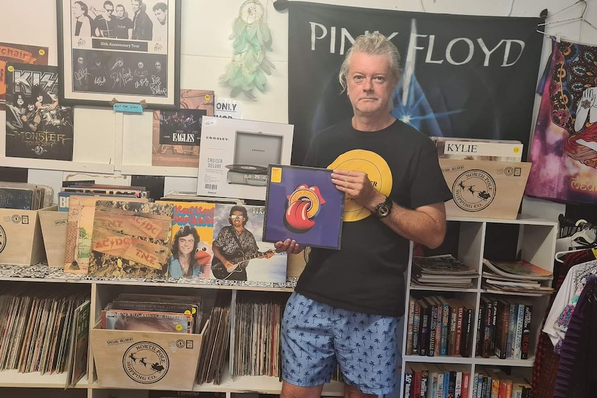 Man with long, grey hair stands in front of record collection and holds record in hands