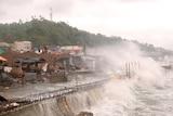 Strong waves batter houses along the coastline
