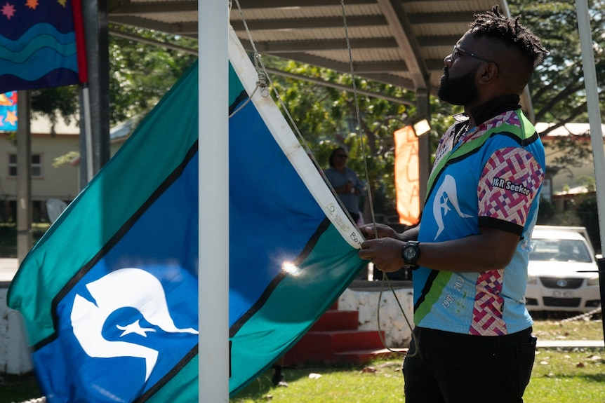 An indigenous man stands at a flag pole preparing to raisea blue, aqua and black striped flag with a 5-pointed white star.
