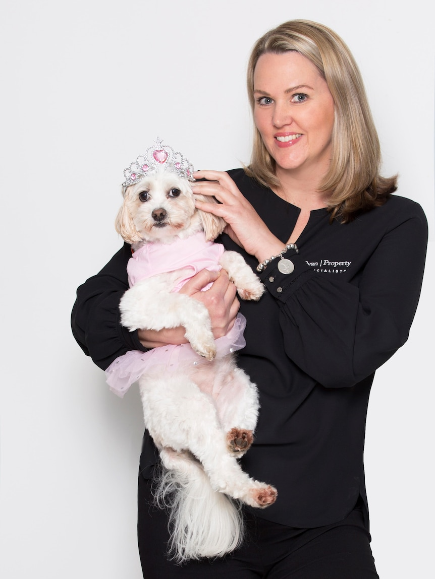 Kym Ryan smiles for a photo while holding her tutu-wearing dog, Missy.