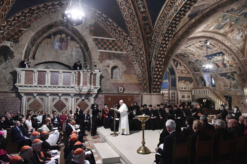 The Pope gives mass in a painted basilica packed with people.