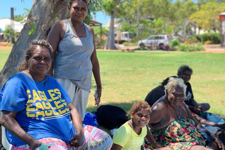 A group of Aboriginal women sit together on the grass under the shade of a tree in Broome.