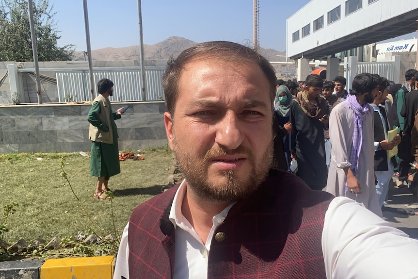 Muftahudin takes a selfie at the Kabul airport with people behind him.