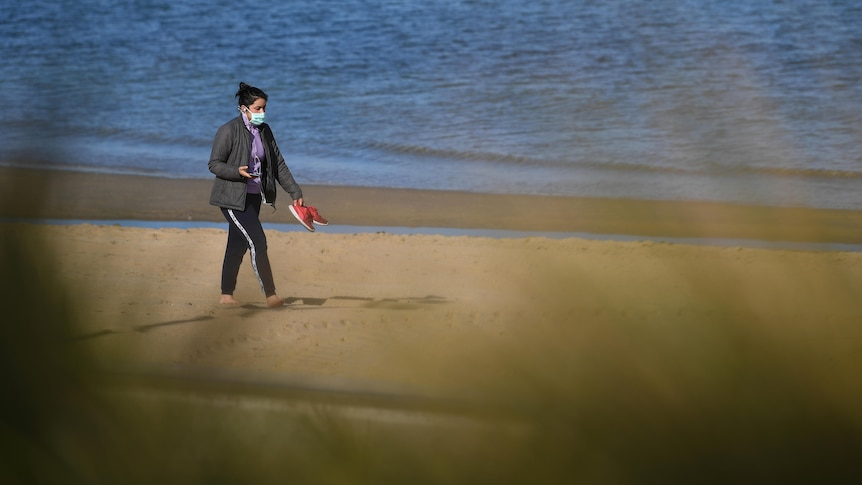 Woman in mask holding red shoes walks on beach