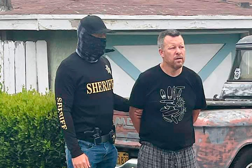 a man in a face mask and black sheriff shirt next to a man with his hands behind his back