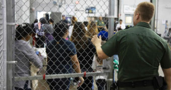 Officer stands at the cage-fenced door