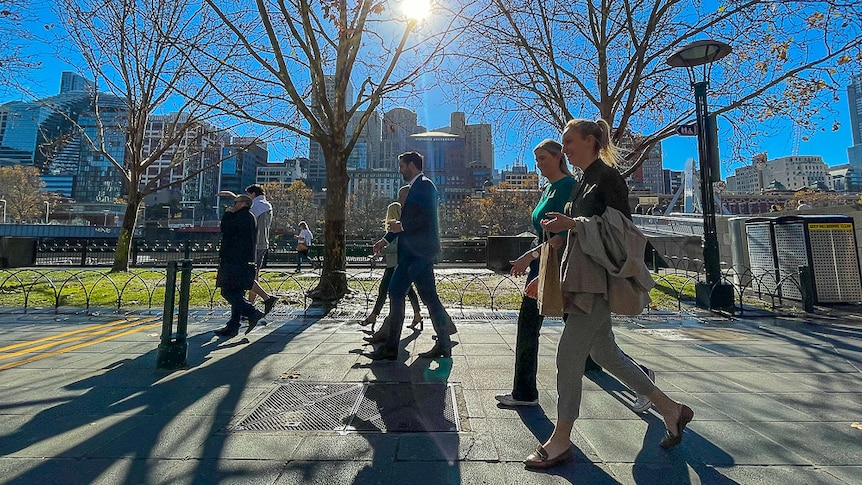 A group of pedestrians walking along a footpath by the Yarra River on a sunny day.