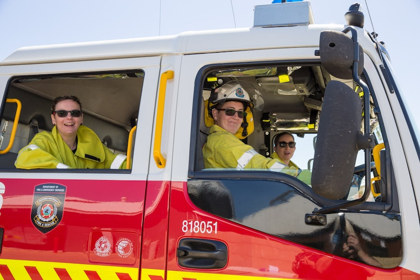 Three women wearing yellow hi-vis sit in a red fire truck smiling out the window