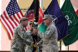A man in a US military uniform hands a rolled up flag to another man.