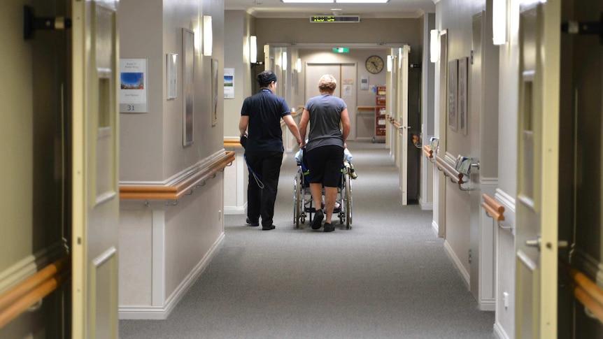 Nurses wheel a resident down a hallway in a Brisbane nursing home