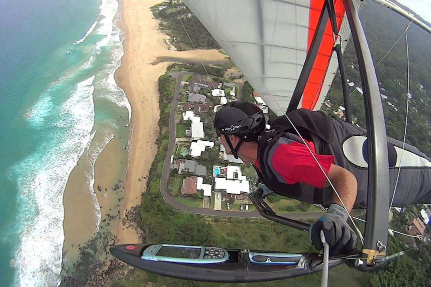 Illawarra hang glider pilot Tony Armstrong flies his glider in the air over Stanwell Park, the view is looking down.