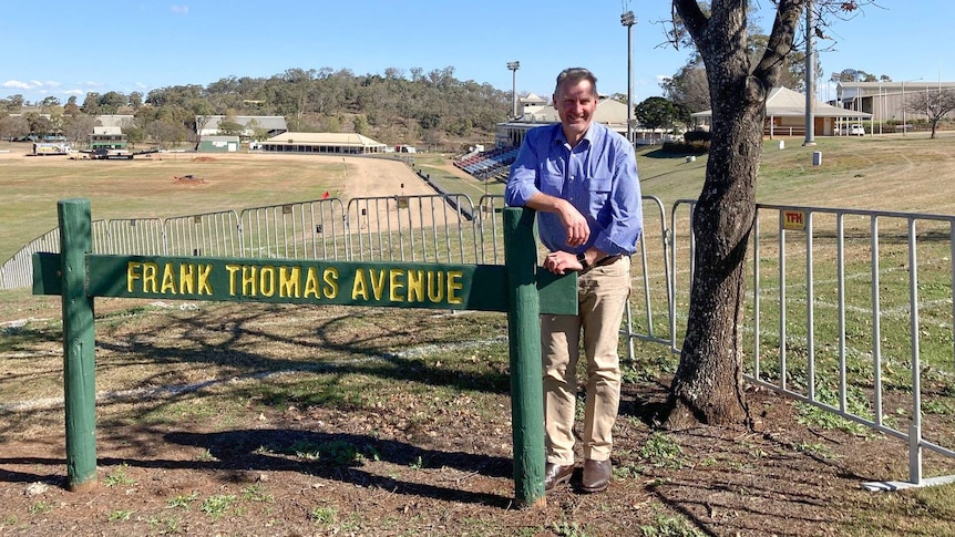 A man stands behind a sign that reads Frank Thomas Avenue