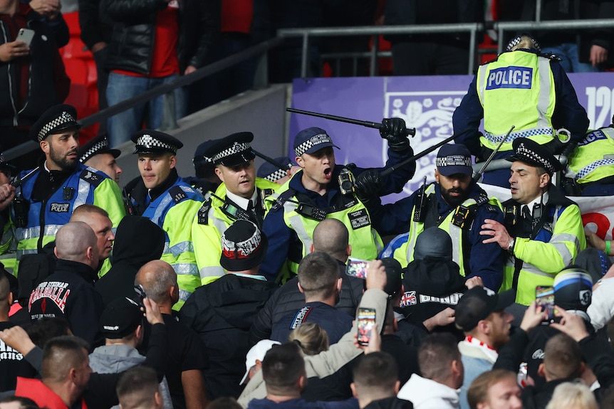 Police with batons raised at a group of men at a football match