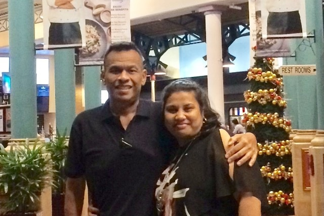 Sprent Dabwido is pictured standing with his arm around his wife Linda Dabwido in a food court.