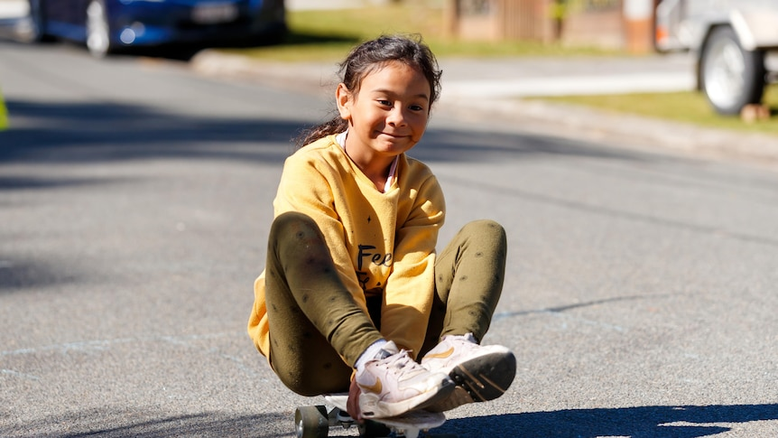 An image of a girl, smiling as she sits on a skateboard rolling down a street in Woodridge
