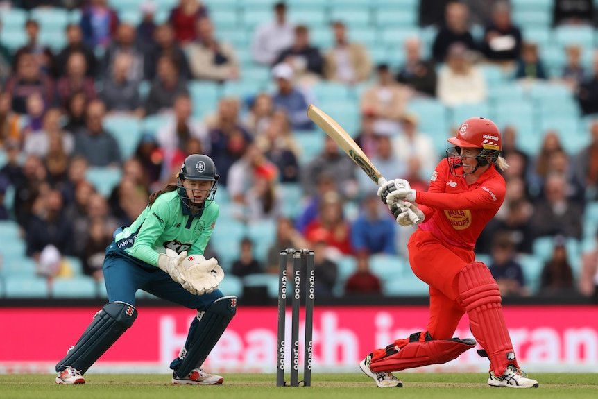 Georgia Redmayne plays a sweep shot as a wicket keeper watches on