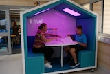 A woman and a boy sit in a large house-shaped pod with purple lighting and workbooks. Behind the pod is a classroom.